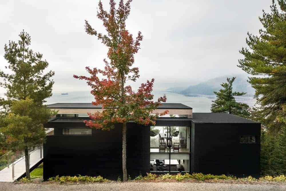 A black-exterior house that offers a panoramic view of the stunning surroundings.