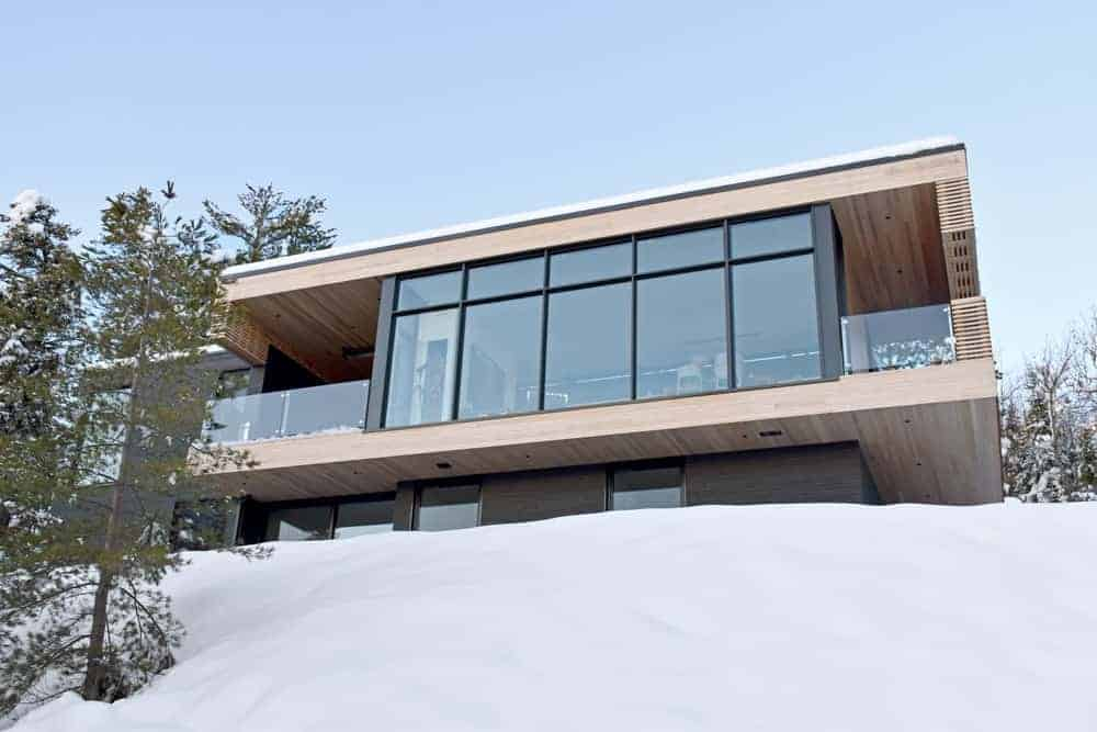A large contemporary residence with tall glass walls and windows along with a wooden exterior.