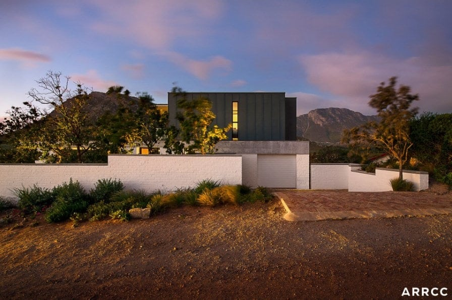 Large contemporary home with a black and white exterior and has a breathtaking view of the surroundings.