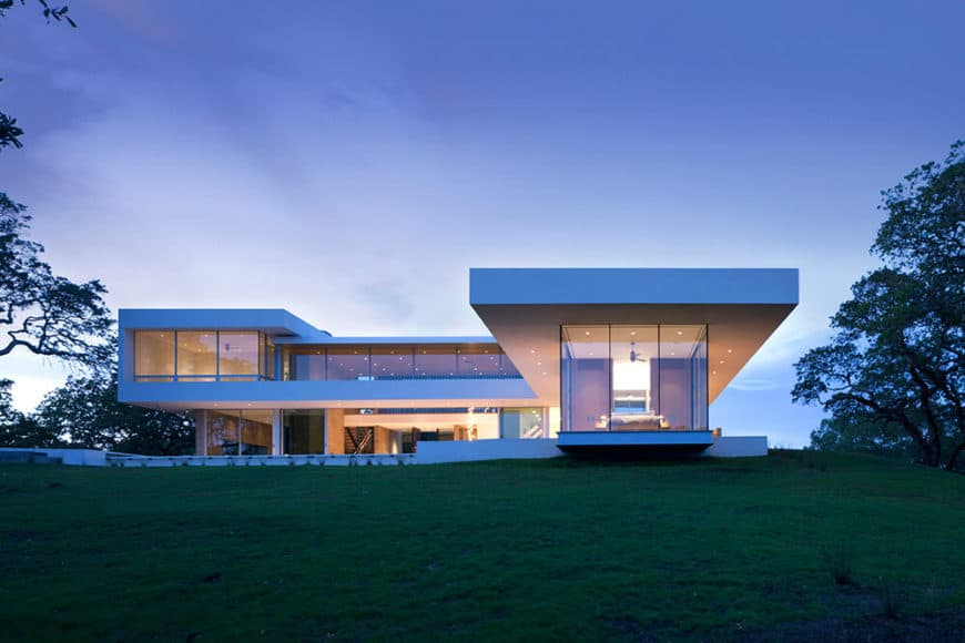 A large contemporary house with a white exterior along with a sprawling lawn area.