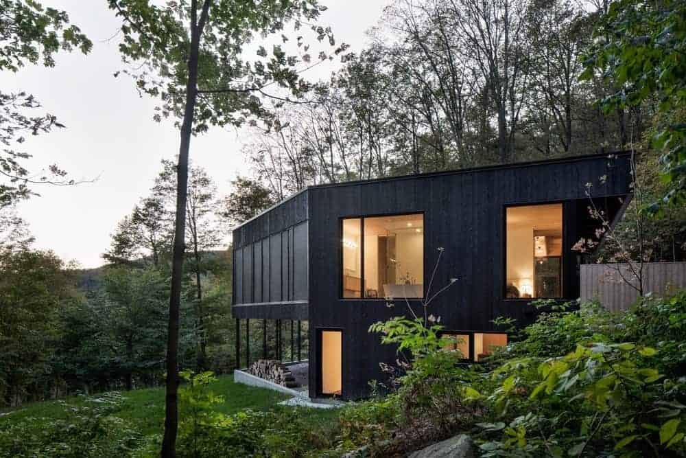 This black-exterior home boasts a stunning view of the surroundings and is surrounded by mature trees.