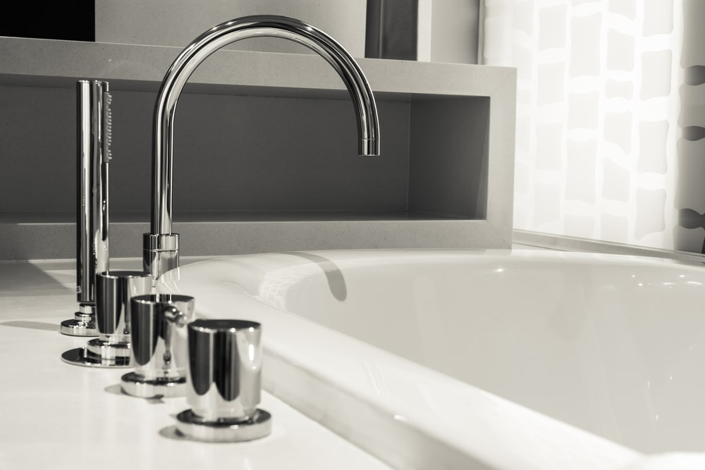 A close look at a roman tub faucet with a stainless steel tone on the side of the porcelain bathtub.