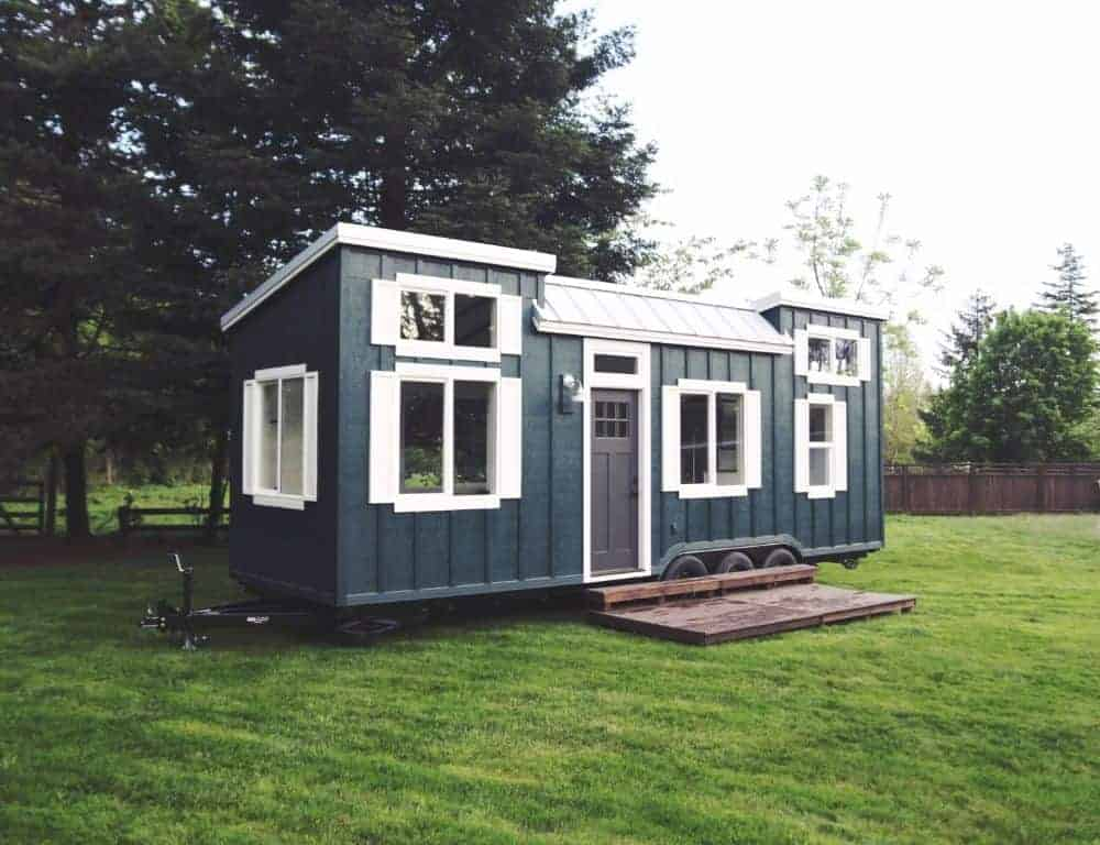A tiny home with a black exterior and is set on a well-maintained lawn area.