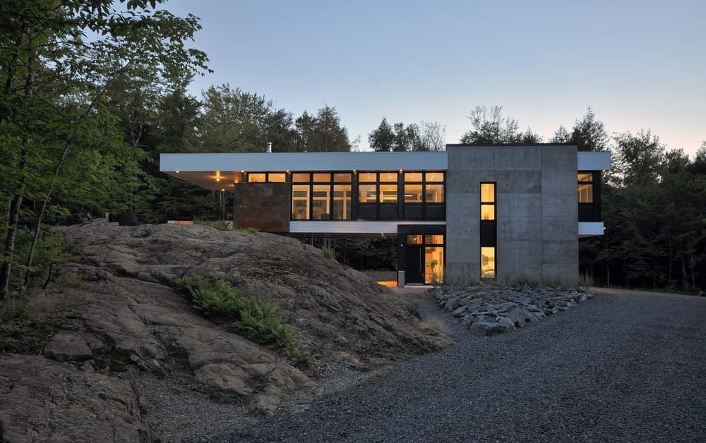 Large contemporary architecture featuring an asphalt driveway. The home is surrounded by mature trees.