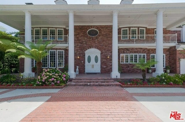 Southern Colonial home exterior with brick driveway.