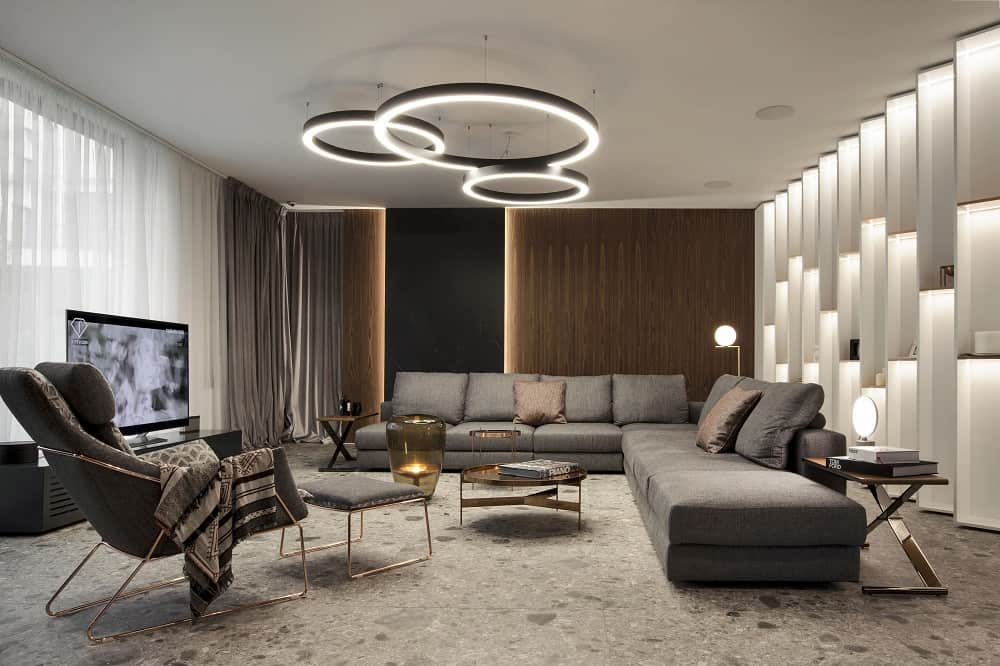 This transitional living room has a unique set of decorative circular lights hanging over the small coffee table across from the two gray sectional sofas complemented by the unique wall with its own lighting.
