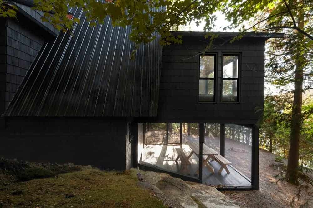 A nicely built house with a black exterior and is surrounded by the beautiful nature.