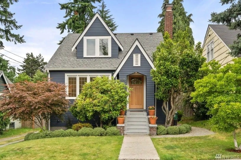 This home boasts a black exterior, a beautiful garden and lawn area and a nice walkway.