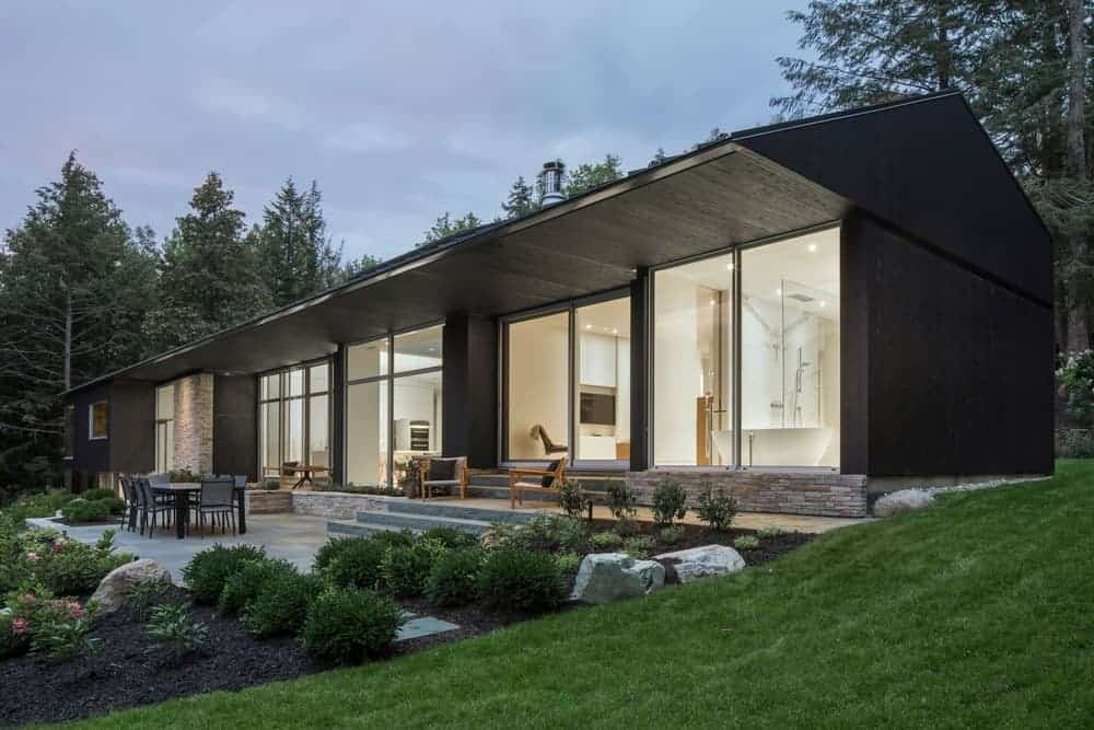 A contemporary house with a black exterior and has a gorgeous garden area along with a patio and an outdoor dining.