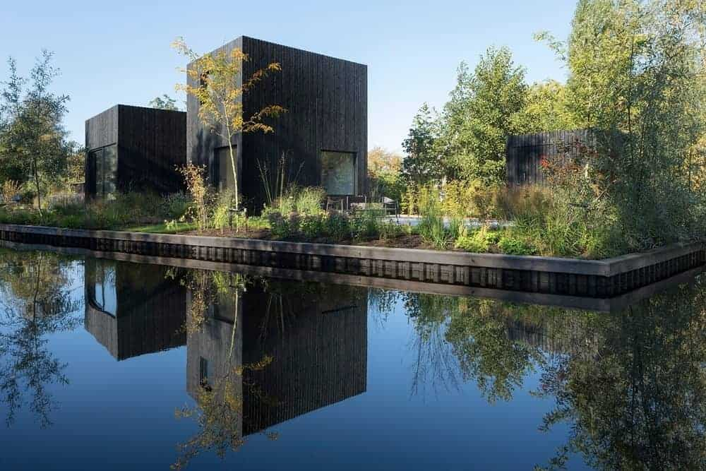 This tiny holiday home boasts black exteriors and has healthy plants and trees outside.