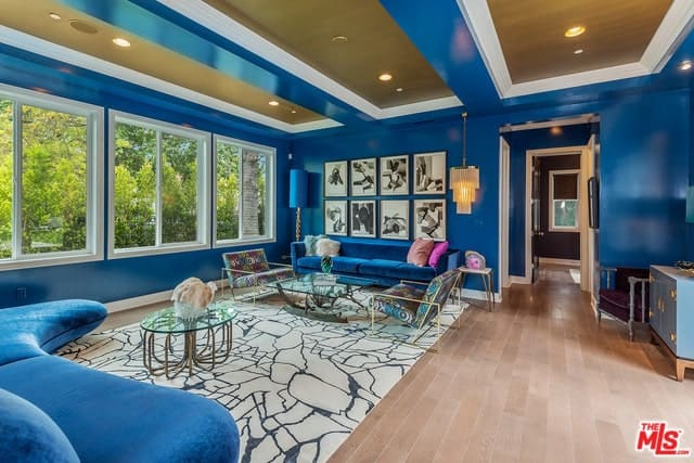 Transitional-style living room interior with lustrous blue tray ceiling, walls, and sofa.