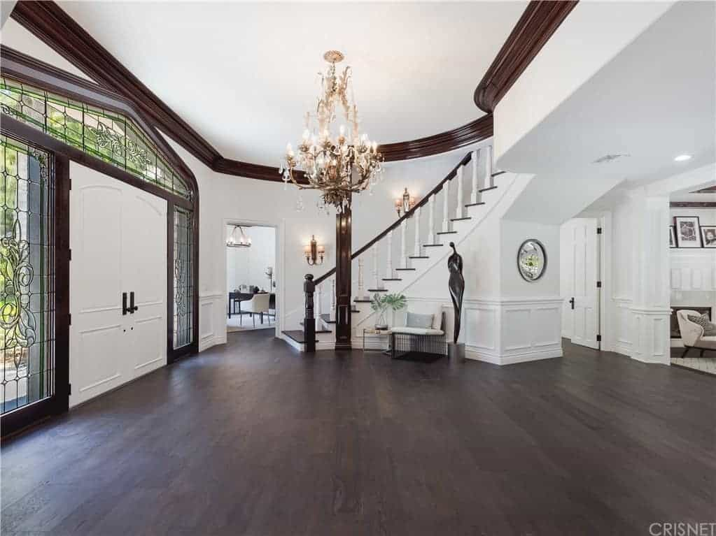 This is a spacious foyer with a hardwood flooring that contrasts the white double doors that have glass side lights and arched transom window, all of which have elegant black lining designs. The majestic chandelier in the middle caps off the aesthetic.