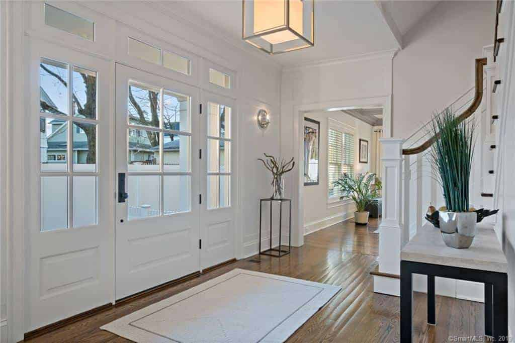This charming foyer has a white main door with built-in French window that matches the design of the side lights and transom window. This is complemented by a modern lantern-like pendant light hanging from the white ceiling.