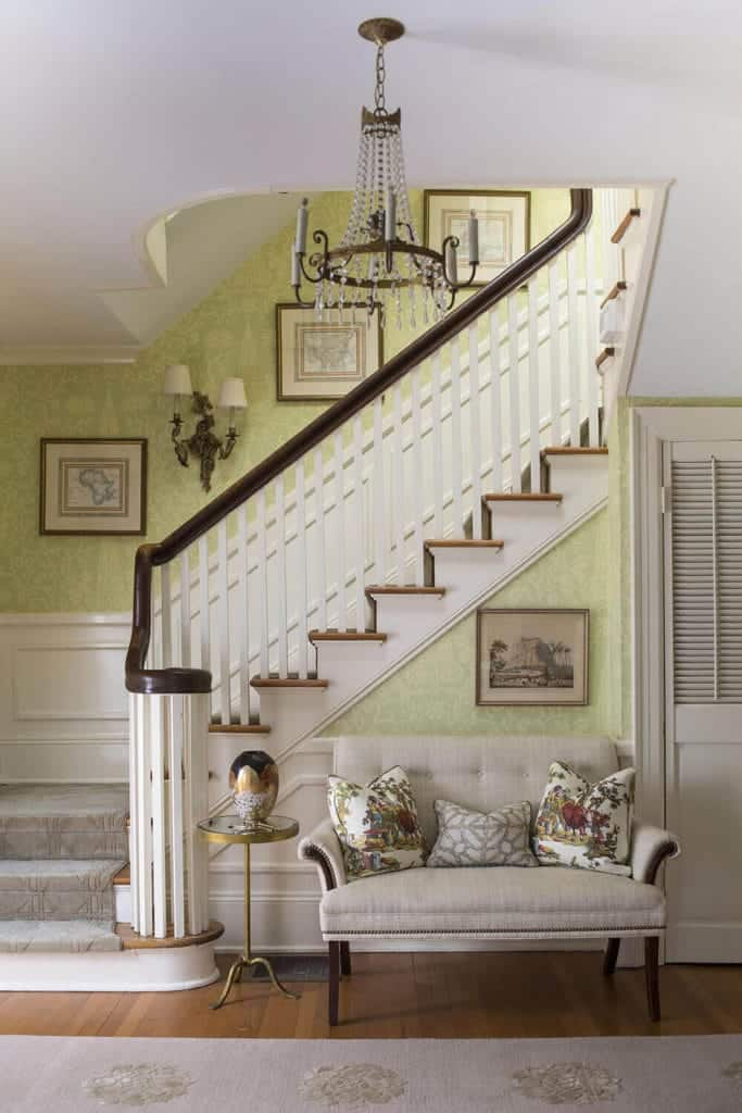 This charming and chic foyer has green floral wallpaper dominating the walls that has white wainscoting paired with a light gray cushioned bench for the waiting guests.