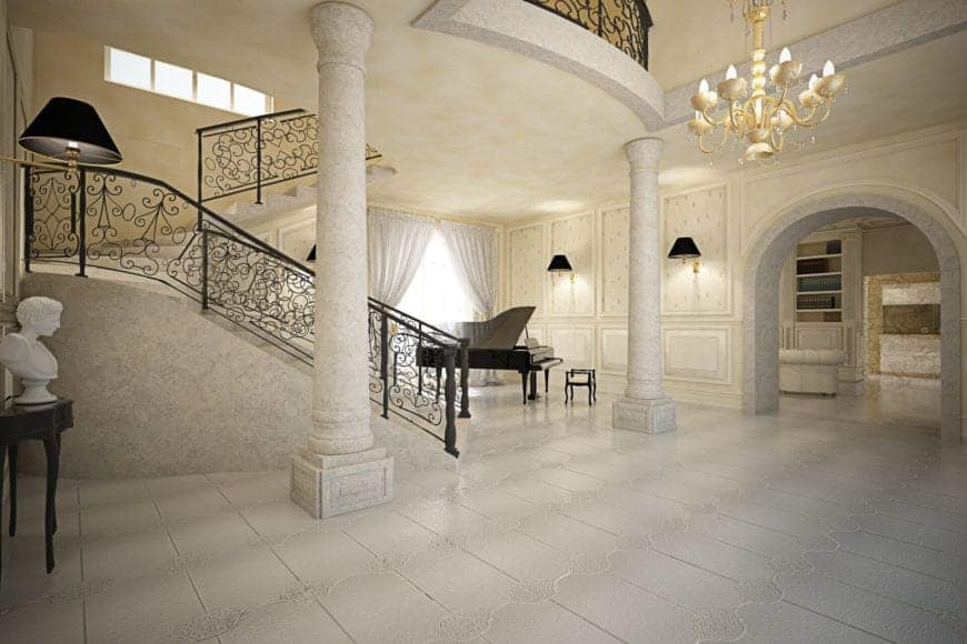 This grand foyer has elegant beige walls paired with a beige chandelier hanging from a high ceiling over the white flooring tiles adorned with a couple of stone pillars and a marble bust for dramatic effect.