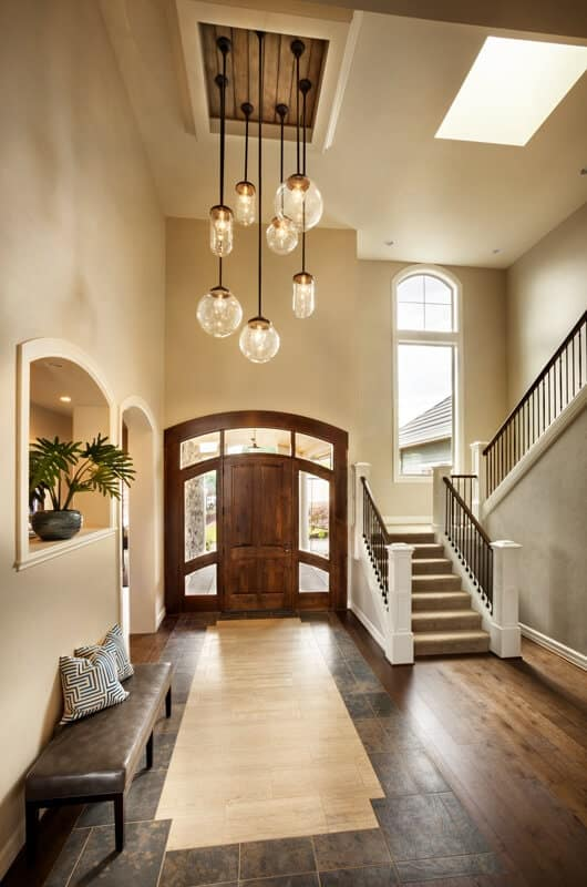 The wooden main door has matching side lights and arched transom window that has glass panels framed with wood. This lets in natural light illuminating the dark floor tiles that contrast the beige walls and high ceiling.