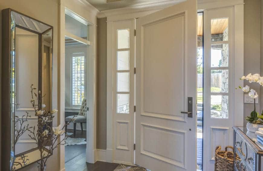 This simple foyer has a warm homey welcome with its white main door flanked with simple side lights blending in with the white molding of the gray walls adorned with a wall-mounted mirror.