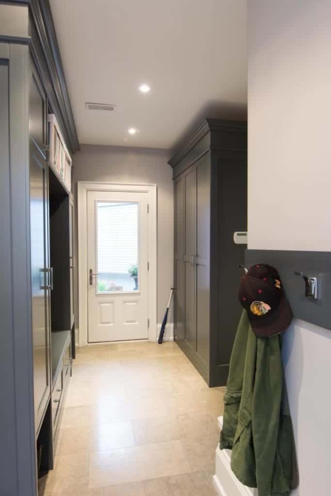 This simple hallway-type foyer has beige marble floors that contrast the dark wooden cabinet on one side and a dark wooden mudroom on the other. These are illuminated by the natural light of the main door's glass window.