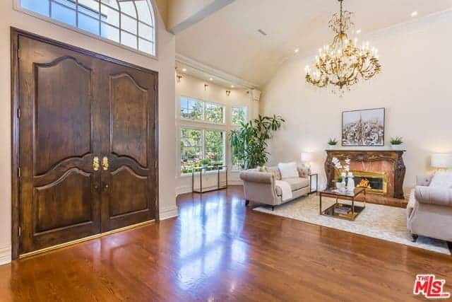 The wooden main doors of this foyer has a arched glass transom window that illuminates the hardwood flooring. This flooring is a nice contrast to the beige walls and high ceiling.