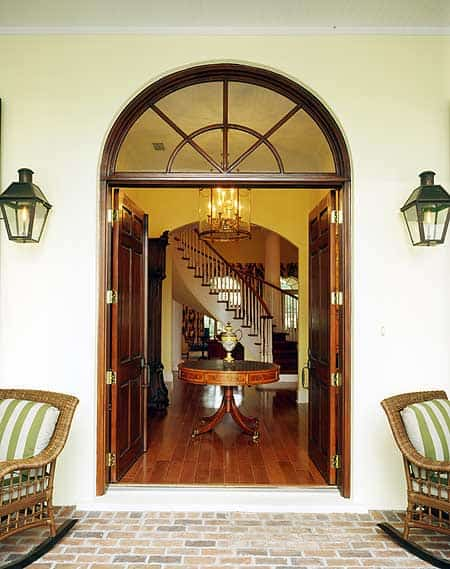 This elegant foyer offers a warm embrace for its guests with its redwood main doors with an arched transom window opening to redwood flooring with a round wooden table in the middle topped with a lantern-like pendant light.