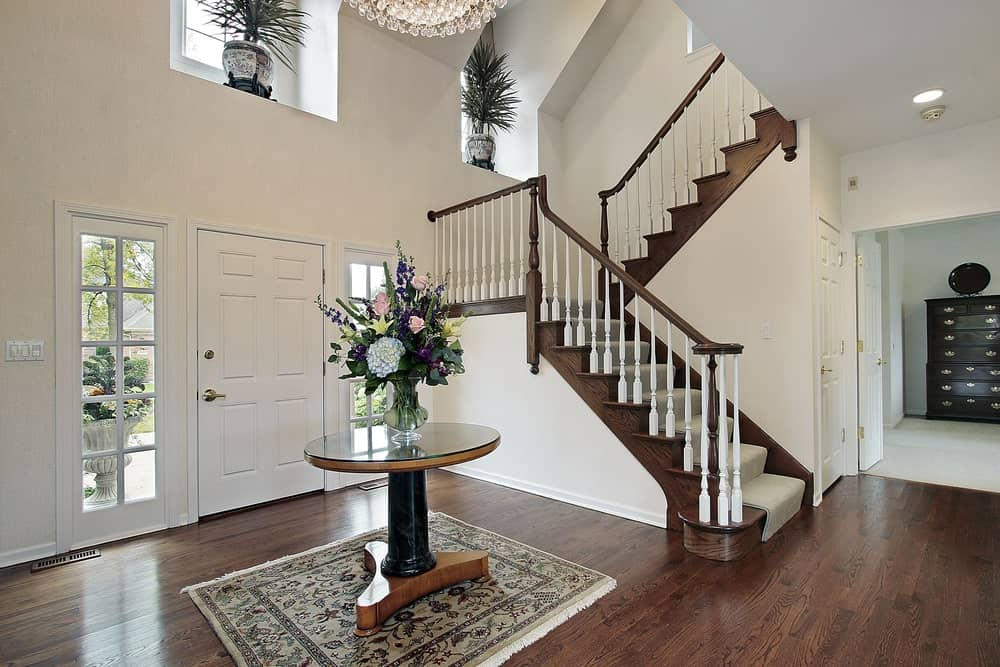 This grand foyer has high beige walls with windows at the top to maximize the vertical space. This is paired with a white main door that has side lights that illuminated the hardwood flooring topped with a circular table.