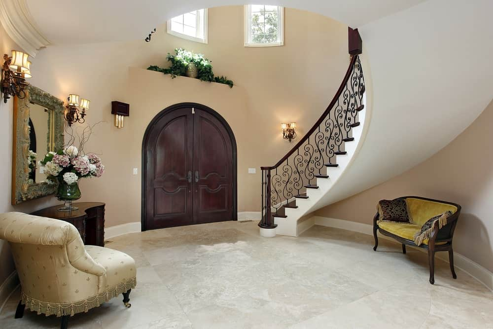 This circular foyer has beige walls and a winding staircase complemented by marble flooring and a arched wooden main door. There is a wooden cushioned bench for waiting guests under the stairs with elegant pillows.