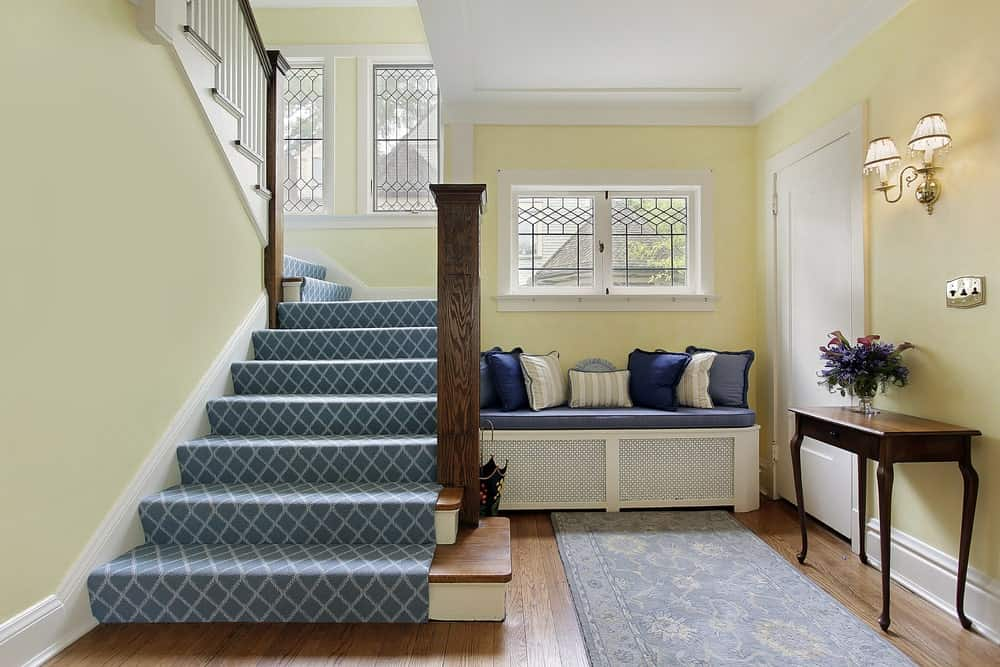 The cheerful yellow walls of this simple foyer is adorned with a white ceiling and molding that match with the cushioned bench on the wall by the stairs that has blue carpeted steps.