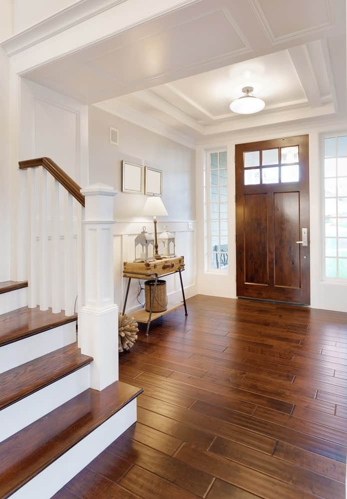 The white tray ceiling is matched with white walls with wainscoting. This is contrasted by the wooden main door that blends in with the hardwood flooring. On the side is a console table made of an old suitcase on a metal pedestal.
