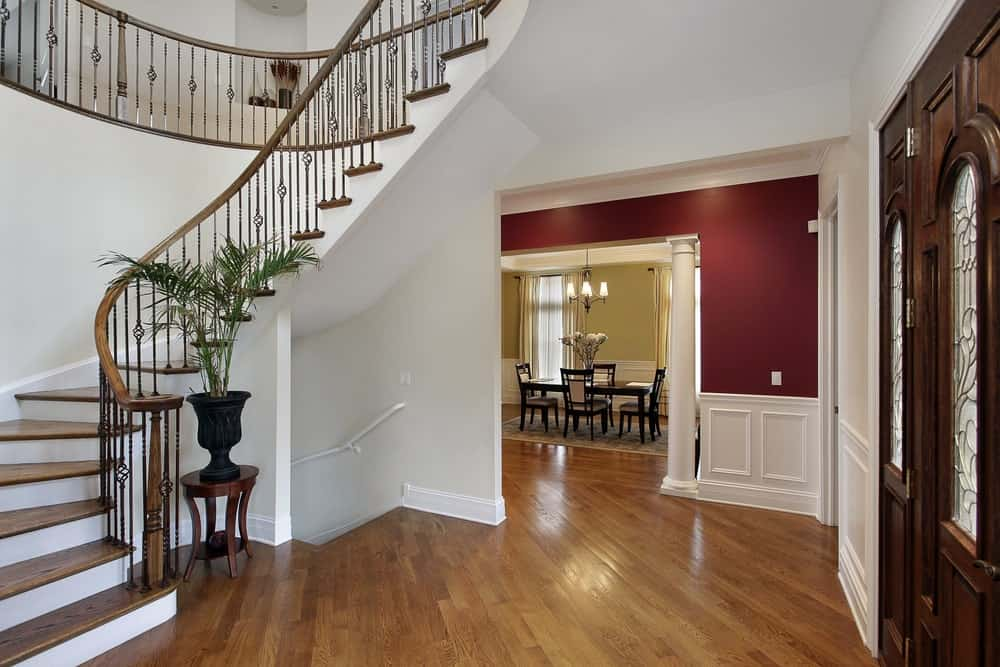 Upon entry of this simple foyer, the hardwood flooring will lead you to the winding staircase that has wooden steps matching the flooring and wooden main doors that contrast the white walls and white ceiling.