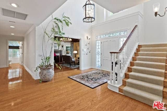 The hardwood flooring of this lovely foyer is topped with a colorful patterned area rug that provide a nice contrast for the white walls, ceiling and main door. This has side lights and transom window filled with intricate designs.