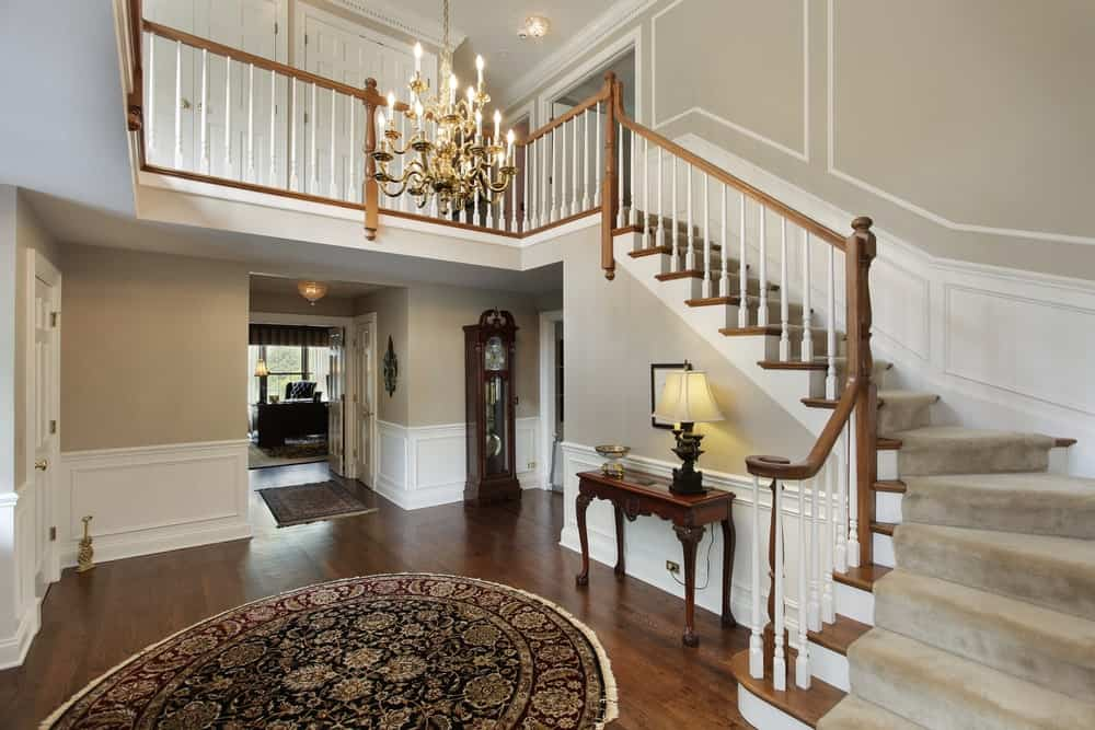 The hardwood flooring of this foyer is topped with a circular patterned area rug complementing the wooden console table that contrasts the white wainscoting of the beige walls.