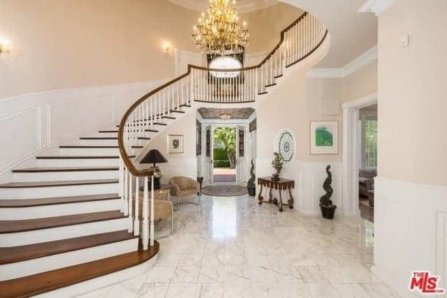 The white marble flooring is a perfect pairing with the white wainscoting of this elegant foyer with beige walls and high ceiling that is paired with a grand multi-tiered chandelier.