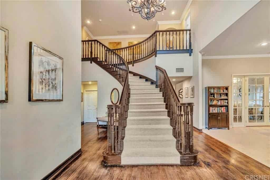 Upon entry of this foyer, the hardwood flooring will lead you directly to the staircase that has wooden railings and carpeted steps that match with the off-white walls adorned with wall-mounted framed artwork.