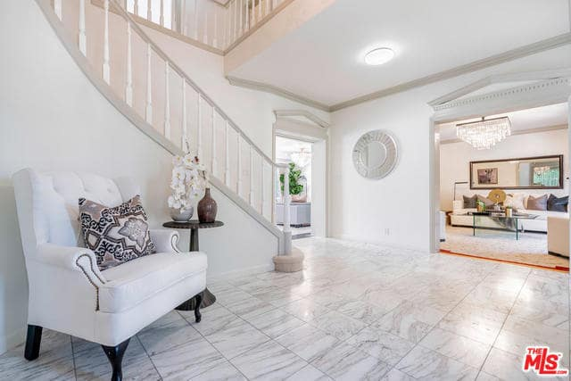 This welcoming foyer pairs its white marble tiled-flooring with white walls and ceiling bearing a white flush-mount lighting. There is a sitting area for guests that has a white cushioned armchair and side table by the stairs.