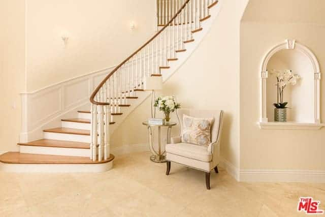 This lovely foyer has a cheerful greeting with its light pink walls and beige flooring that is paired with a sitting area that offers the guests a cushioned pink armchair at the nook by the stairs.