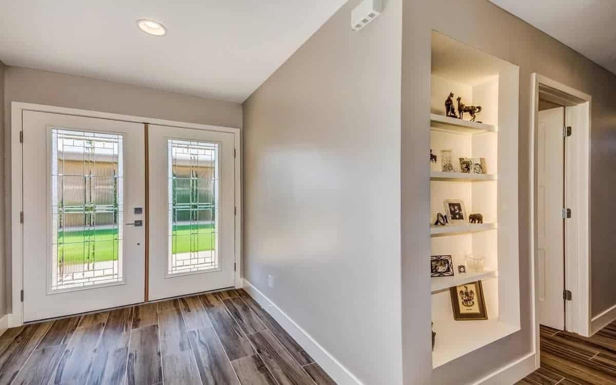This small and simple foyer has glass double doors for its main entrance. These doors have white framing that matches with the molding of the light gray walls that contrast the hardwood flooring.
