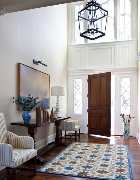 The colorful patterned area rug over the hardwood flooring provides a dash of color to the white walls and high ceiling. The abundance of natural light is provided by the tall windows above the wooden main door.