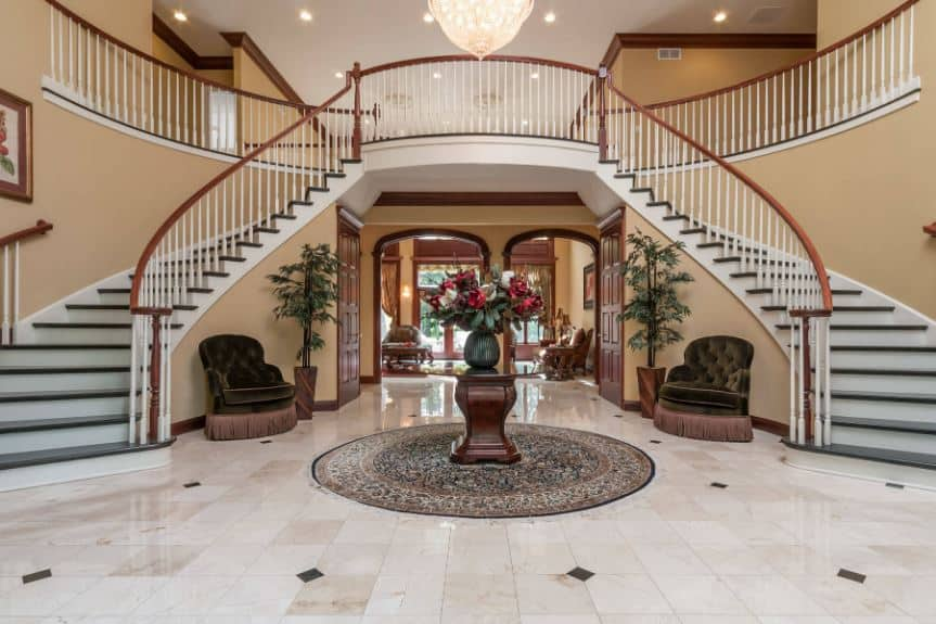 This is a grand spacious foyer with a round glass-top table in the middle of the marble flooring with a green flower vase. there is also a pair of cushioned green armchairs by the stairs.