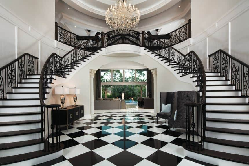 This grand foyer has a black and white aesthetic with its checkered flooring, stairs that have black railing and steps paired with white walls and white walls adorned with black furniture.