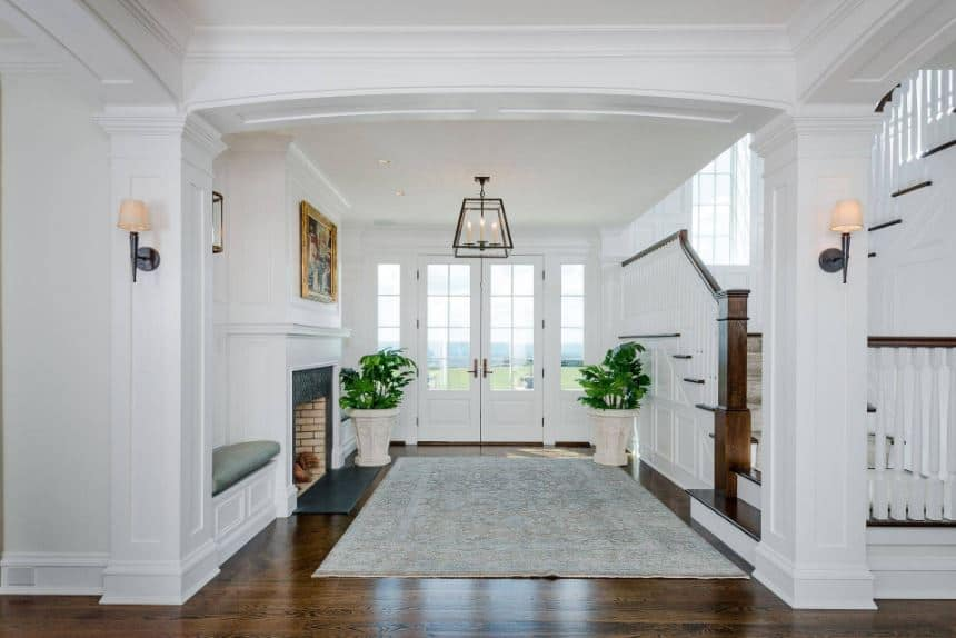 This small foyer offers a warm embrace welcome for the guests with its fireplace built into the white wall topped with a wall-mounted framed painting.