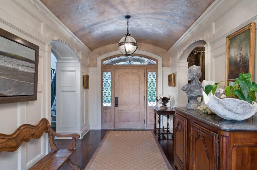 The beige wooden main door has elegant side lights and arched transom window that blend in with the beige cove ceiling that has a spherical pendant lantern hanging over the hardwood flooring and its beige area rug.