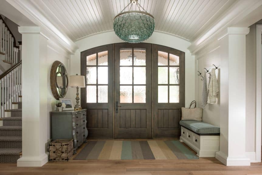 The wooden main door has frosted glass windows on it that matches the side lights bringing an abundance of natural lights on the white walls and white cove ceiling that has a crystal pendant light.