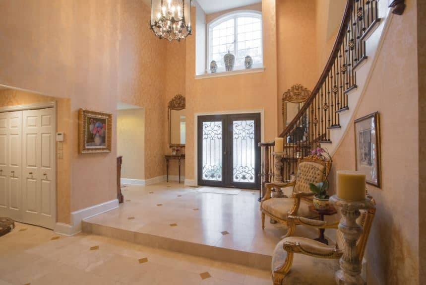 The delightful peach-colored walls and beige marble flooring work together to provide a warm welcome to the guests in this high-ceiling foyer as well as the pair of elegant cushioned armchairs on the side.