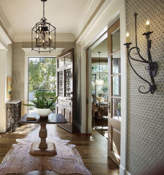 This foyer has walls covered in wallpaper that has moss green peacock patterns paired with white molding that blend in with the white ceiling contrasted by the hardwood flooring adorned with a animal print area rug.