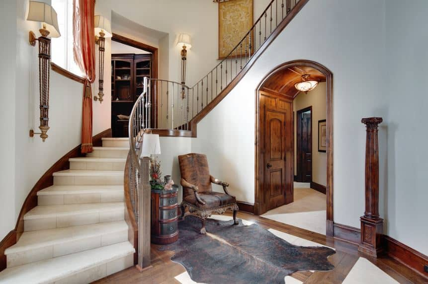 This is a nice foyer with white wall accented with wooden elements on its moldings and arched entryways. This is augmented by the hardwood flooring with an animal print area rug.