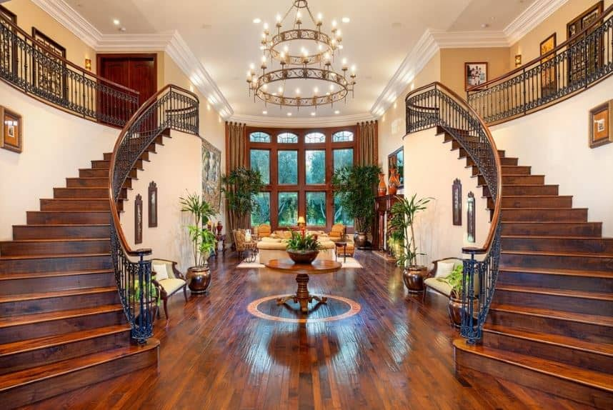 This wide and spacious grand foyer has hardwood flooring topped with a round wooden table that bears a potted plant on top. This is illuminated by the the immense two-tiered chandelier hanging from the high white ceiling.