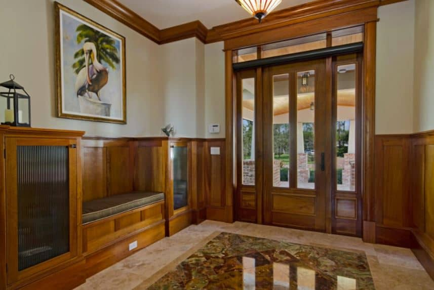 This simple foyer has a wooden main door and side lights that have glass panels bringing in natural light to the marble flooring and wooden built-in bench on the side flanked by cabinets.