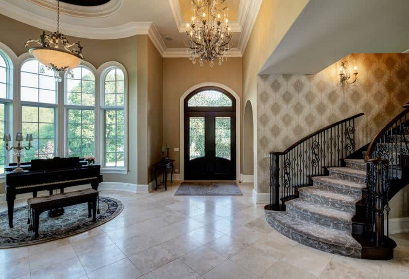 This grand foyer has a crystal chandelier hanging from the high tray ceiling that reflects the white marble flooring that is illuminated by the tall windows where a grand piano is placed for dramatic effect.