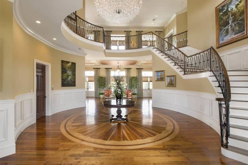 This circular grand foyer has sleek wooden flooring adorned with a circular wooden table in the middle bearing a flower vase. The flooring is contrasted by beige walls with white wainscoting and topped with a grand crystal chandelier.