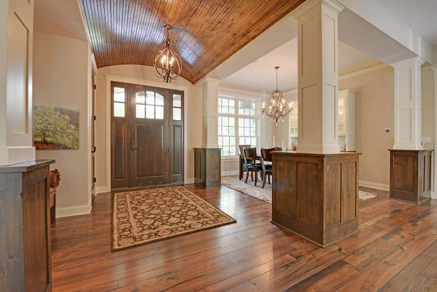 The hardwood flooring that is topped with a patterned area rug is reflected by the wooden cove ceiling with a lantern-like pendant light illuminating the wooden door with wooden side lights.